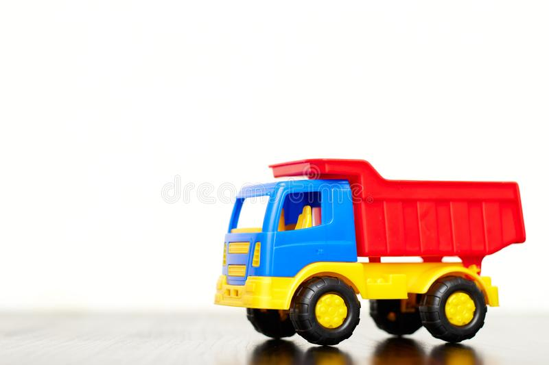 Children`s toy truck, a multi-colored plastic dump truck on a white background, copy space. toys for boys royalty free stock photo