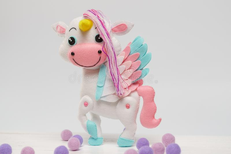 Children`s toy unicorn made of felt on a white background stock photos