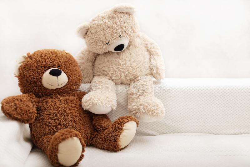 Children`s toys - bears of brown and beige color are sitting on the sofa. Selective focus royalty free stock photography