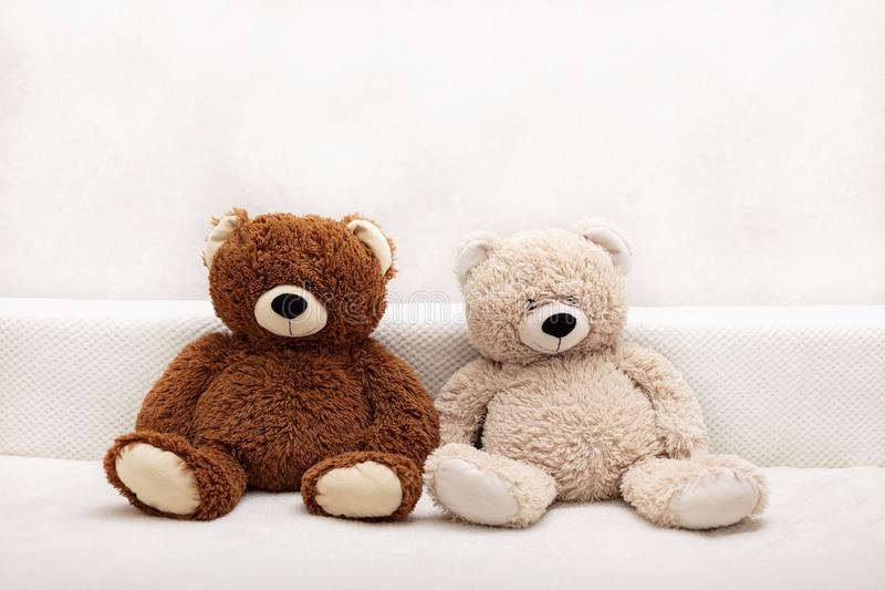 Children`s toys - bears of brown and beige color are sitting on the sofa. Selective focus stock photo