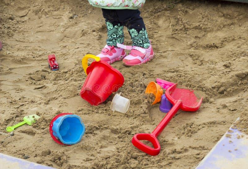Children`s toys in the sandbox and children`s legs scapula stock photo