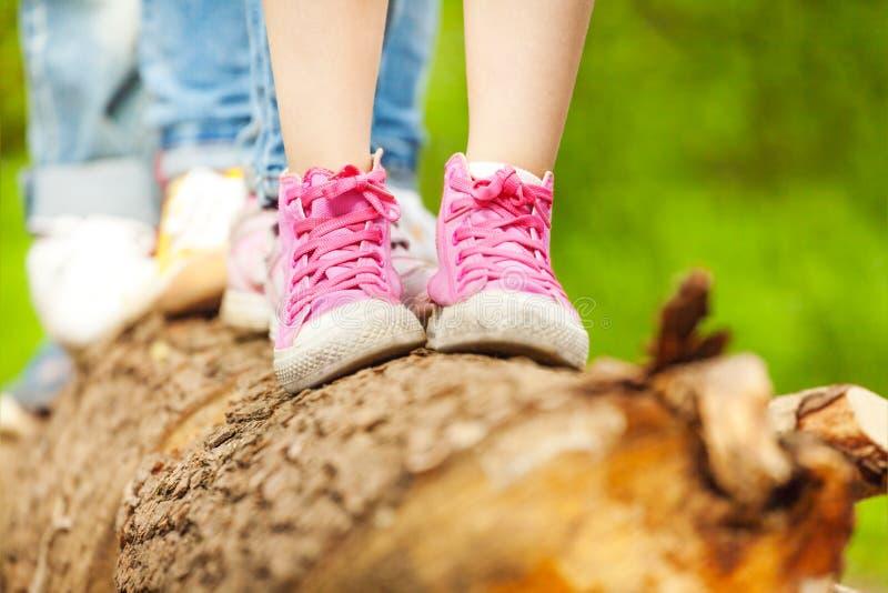 Children& x27; s voeten in roze tennisschoenen die zich op een logboek bevinden stock afbeeldingen