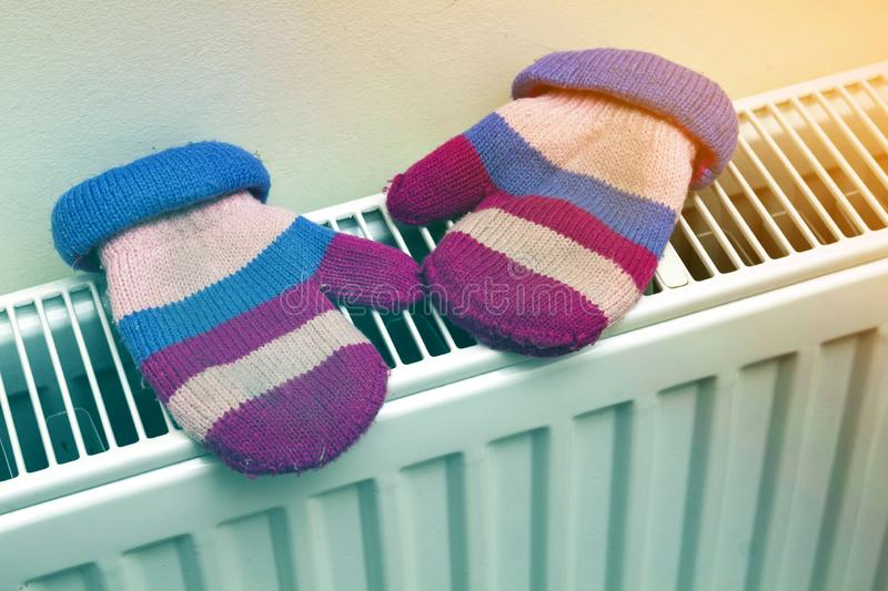Children`s warm hand knitted striped woolen gloves drying on heating radiator after winter day outside.  stock photos
