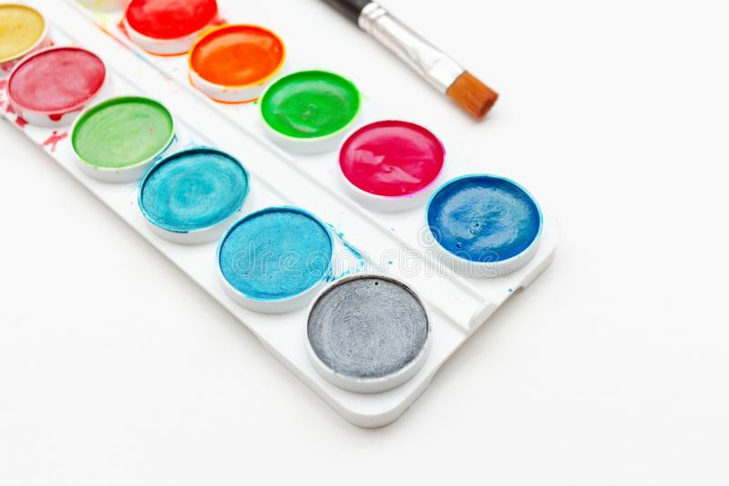 Children`s watercolor paints and brush in a white box on a light background. royalty free stock photo