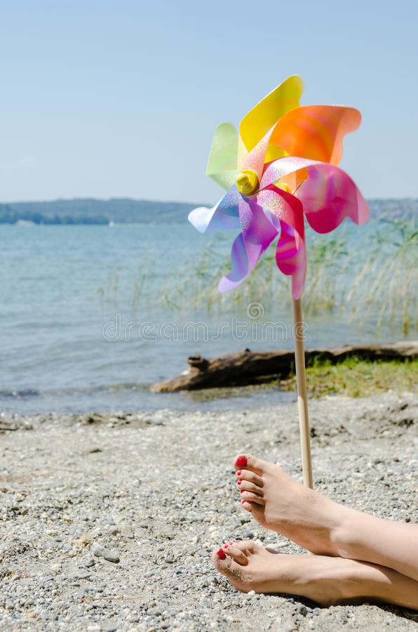 Children`s windmill and female legs at the beach royalty free stock photos