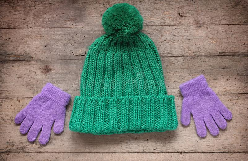Children`s winter accessories: hat and gloves. Rustic wooden bac. Kground. Pastel green and purple colors royalty free stock photography