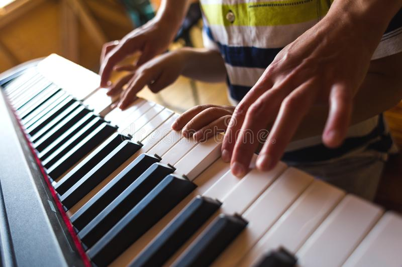Children`s and women`s hands on the piano keys. A woman teaches her son to play the piano. The boy masters the keyboard musical instrument. A child learns music stock image