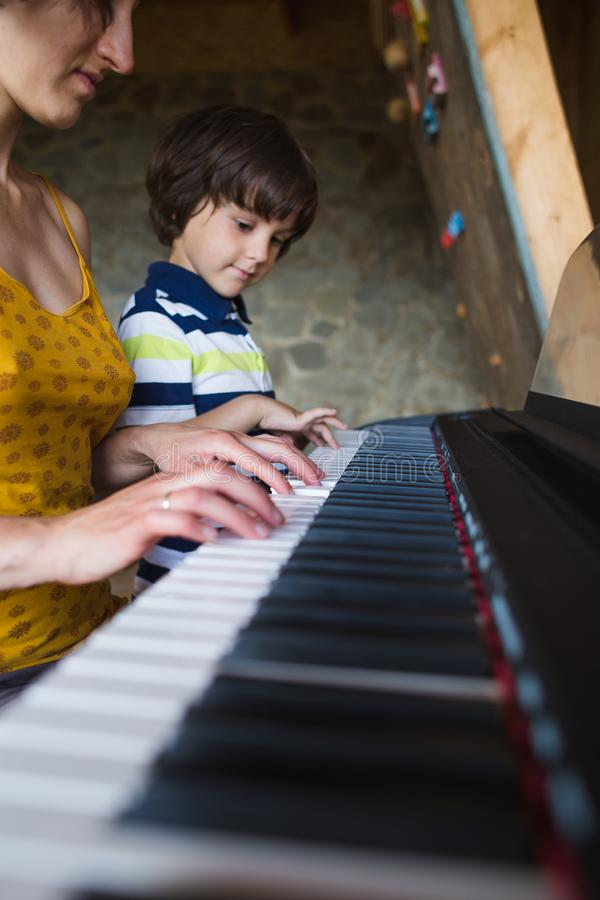 Children`s and women`s hands on the piano keys. A women teaches her son to play the piano. The boy masters the keyboard musical instrument. A child learns music royalty free stock photography