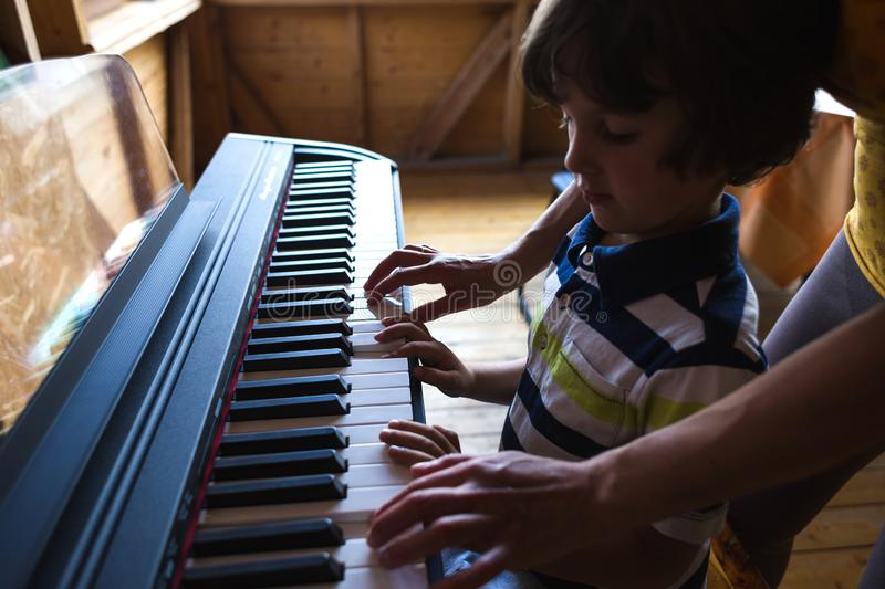 Children`s and women`s hands on the piano keys. A women teaches her son to play the piano. The boy masters the keyboard musical instrument. A child learns music stock image