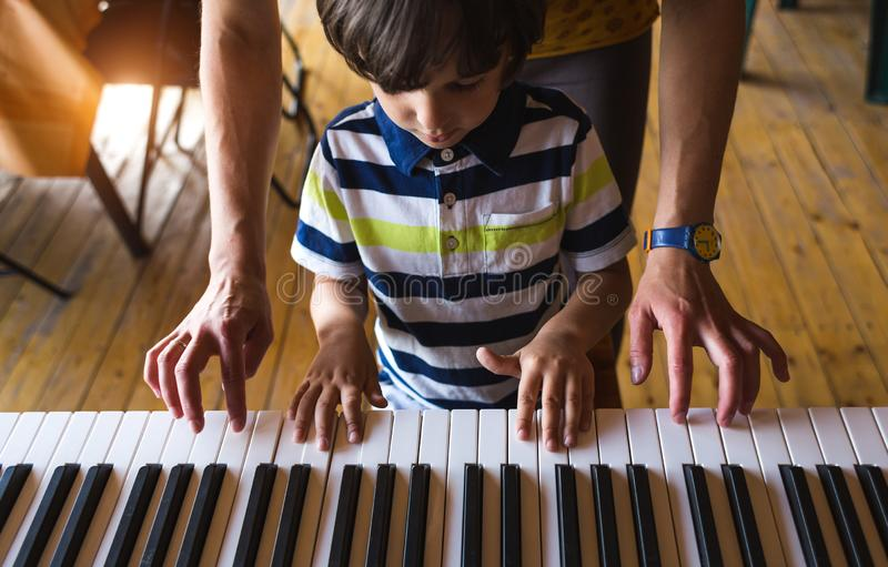 Children`s and women`s hands on the piano keys. A women teaches her son to play the piano. The boy masters the keyboard musical instrument. A child learns music stock photos