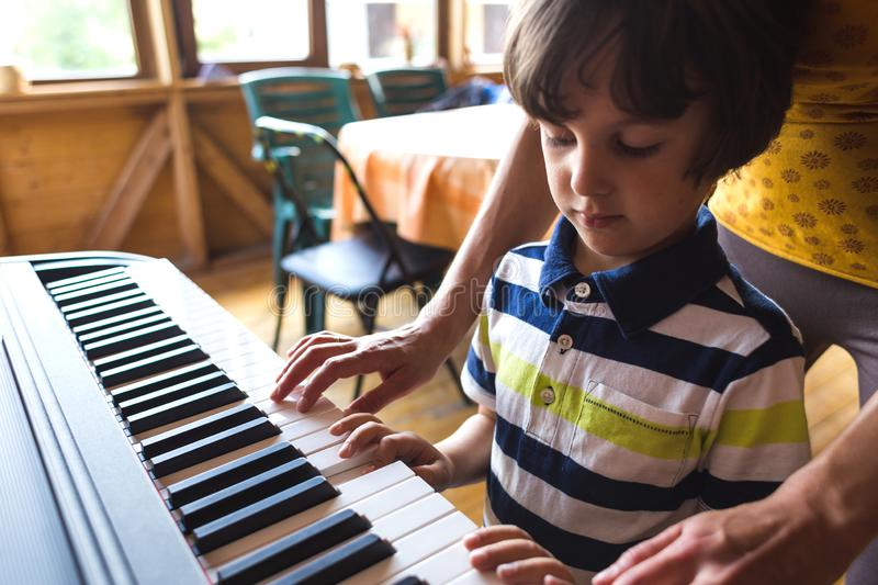 Children`s and women`s hands on the piano keys. A women teaches her son to play the piano. The boy masters the keyboard musical instrument. A child learns music royalty free stock images
