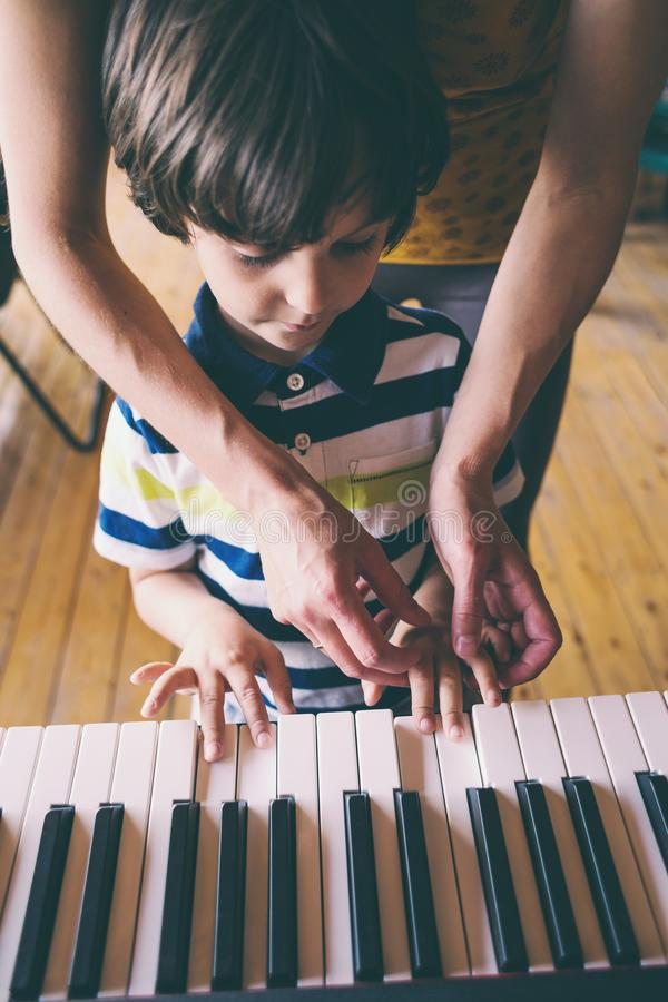 Children`s and women`s hands on the piano keys. A women teaches her son to play the piano. The boy masters the keyboard musical instrument. A child learns music royalty free stock image