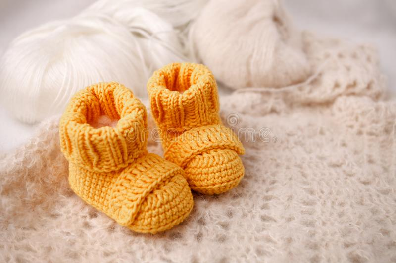 Children`s yellow knitted booties on a light gentle background. The concept of expecting a child, motherhood, parenthood royalty free stock photo