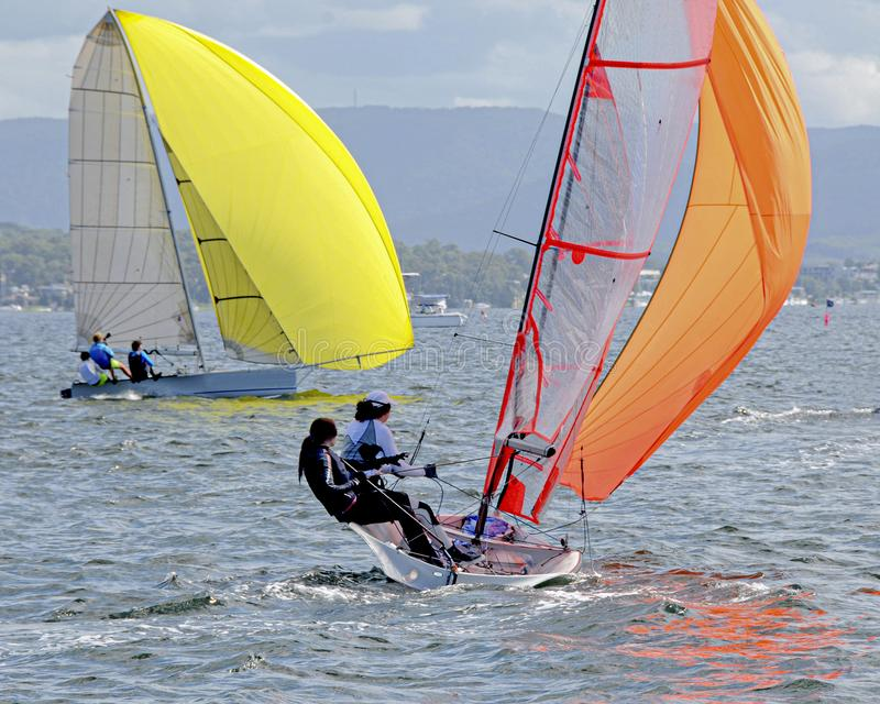 Children Sailing small sailboats with yellow and orange sails on an inland waterway. Children Sailing small sailboats with yellow and orange sails in competition stock photos