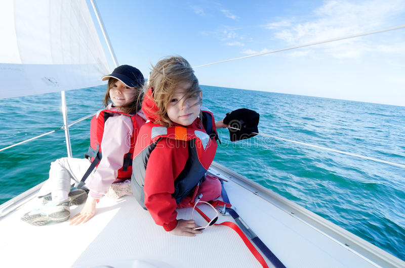 Children sailing on yacht. Two cute young girls sailing on yacht, blue sea in background