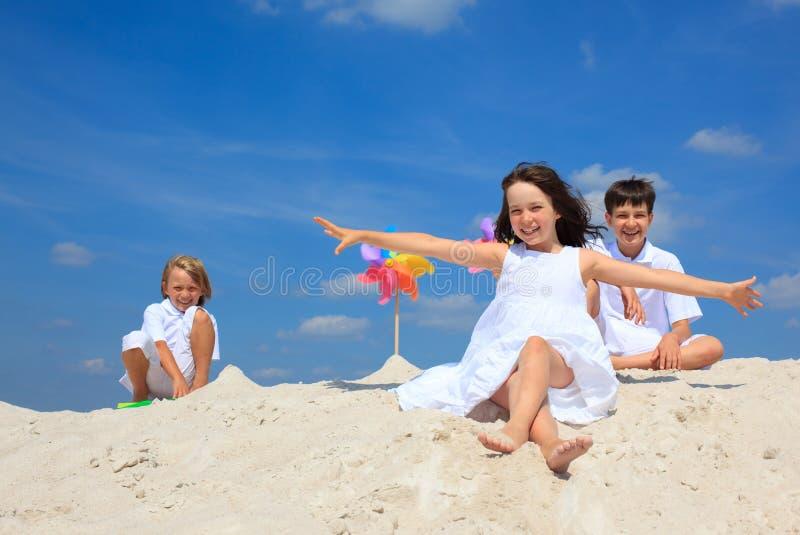 Children in sand on beach stock photos