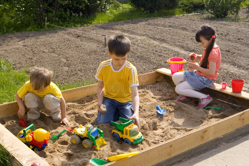 Children in sand-box stock image