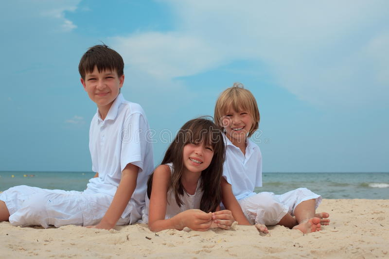 Children on sandy beach. Three happy, smiling children on a sandy beach royalty free stock photography