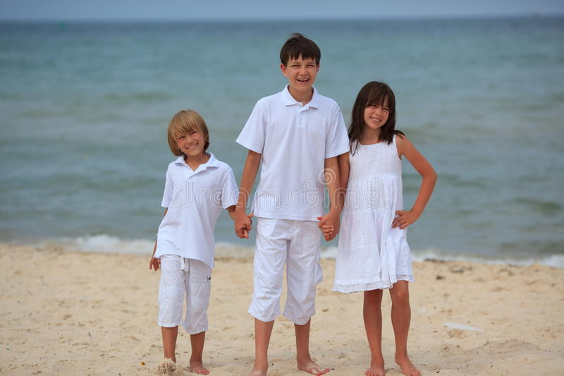 Children on sandy beach. Three happy, smiling children standing on a sandy seaside beach stock photo