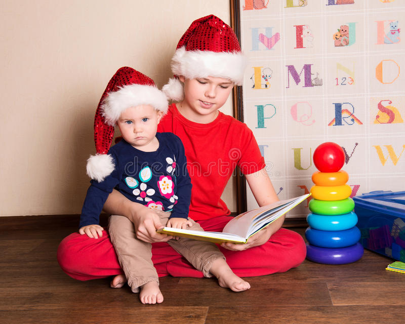 Children in Santa hats reading a Christmas book. Big brother reading to his little baby sister in the nursery. stock image