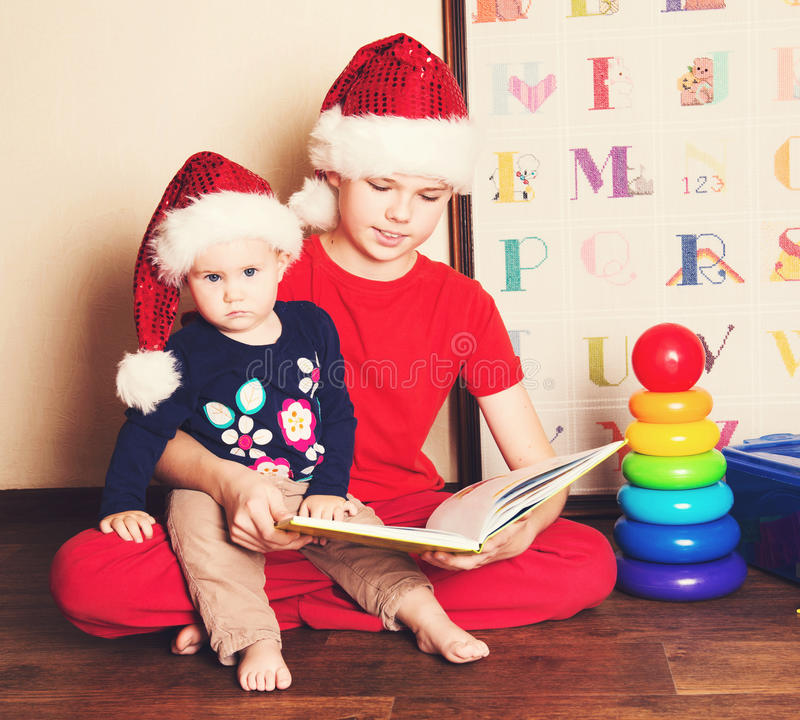 Children in Santa hats reading a Christmas book. Big brother reading to his little baby sister in the nursery. royalty free stock image