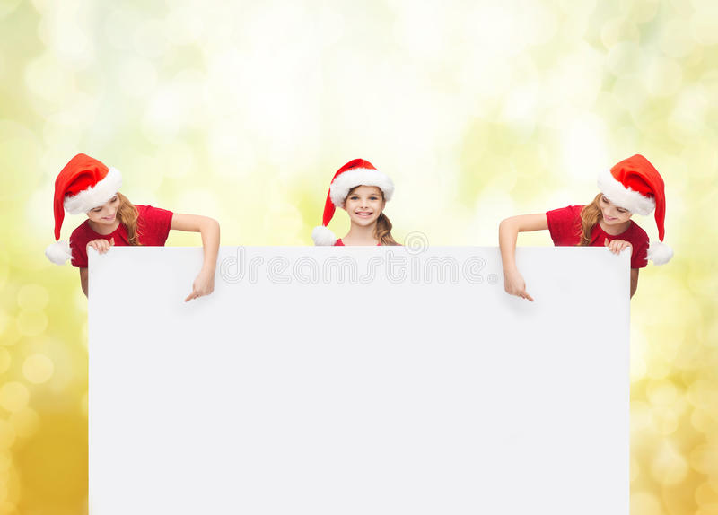 Children in santa helper hats with blank board royalty free stock image
