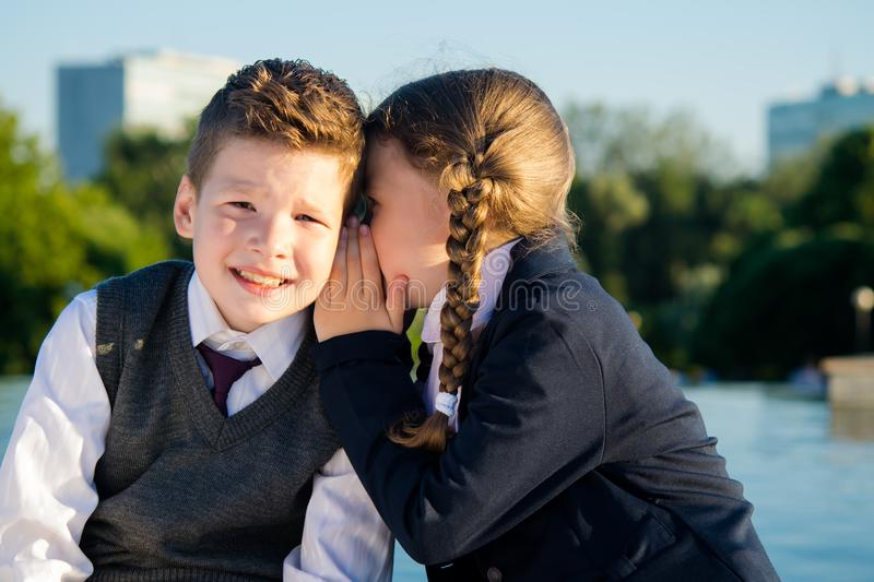 Children of school age tell each other their secrets, on the street royalty free stock photography