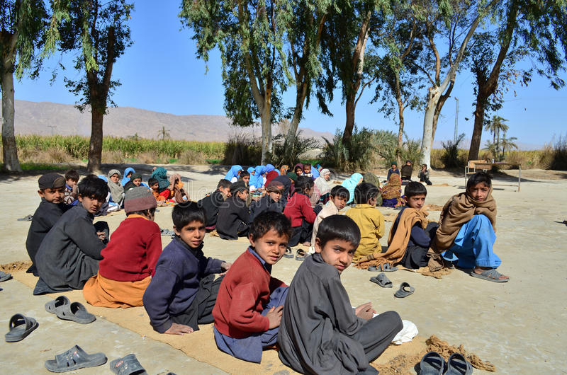 Children School on Ground!. This was the school i found in a village near Dera Ismail Khan city of Pakistan where young kids were sitting on mats to carry on stock photo