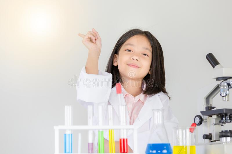 Children scientist concept, Happy little girl is presenting at the laboratory in science classroom royalty free stock photo