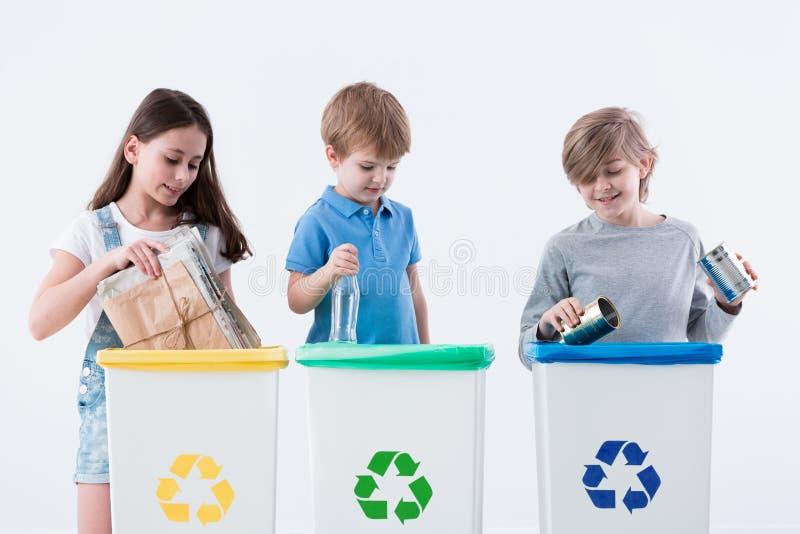 Children segregating paper into bins. Children segregating paper, glass and metal into yellow, green and blue bins stock images