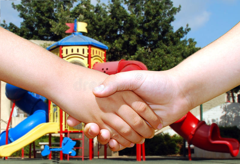 Children shaking hands. Two children shaking hands in front of a colorful playground royalty free stock photo