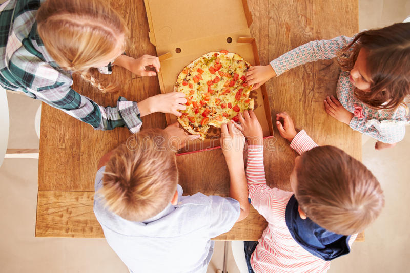 Children sharing a pizza together, overhead view royalty free stock photography