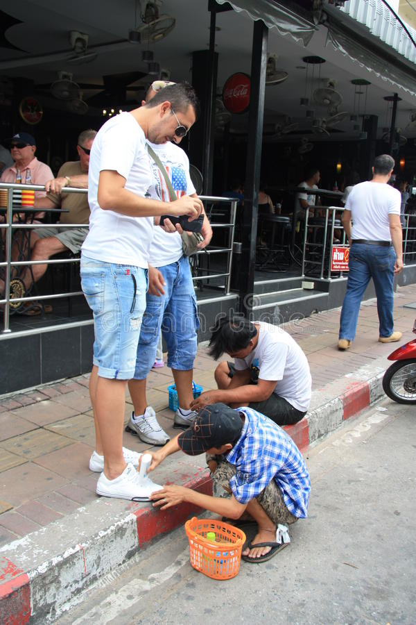 Children Shoeblacks in Thailand. Children Shoeblacks cleaning shoes in the street of Pattaya, Thailand royalty free stock photography