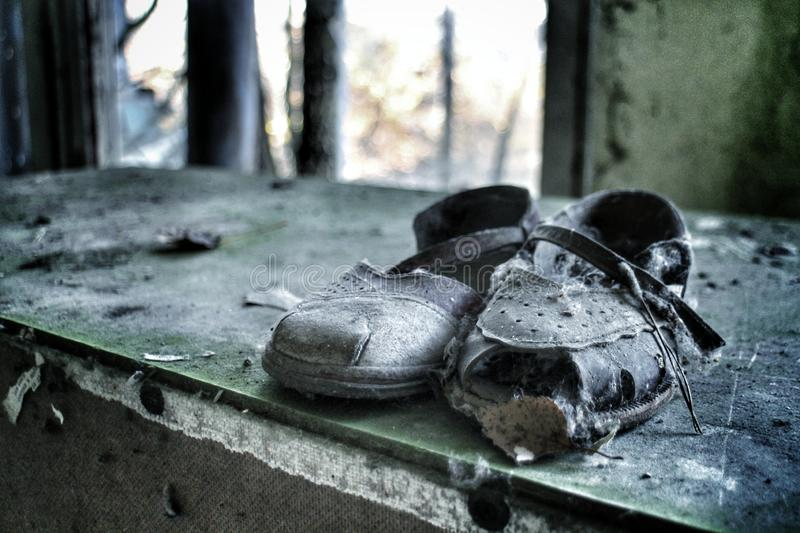Children shoes left behind in the Chernobyl exclusion zone. Small girl`s shoes are left behind inside an abandoned building in Pripyat, in the Chernobyl royalty free stock images
