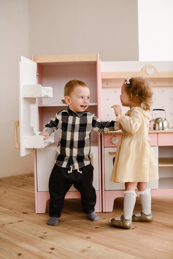 Children or siblings concept. Sweet toddler girl and boy playing with toy kitchen in light room stock image