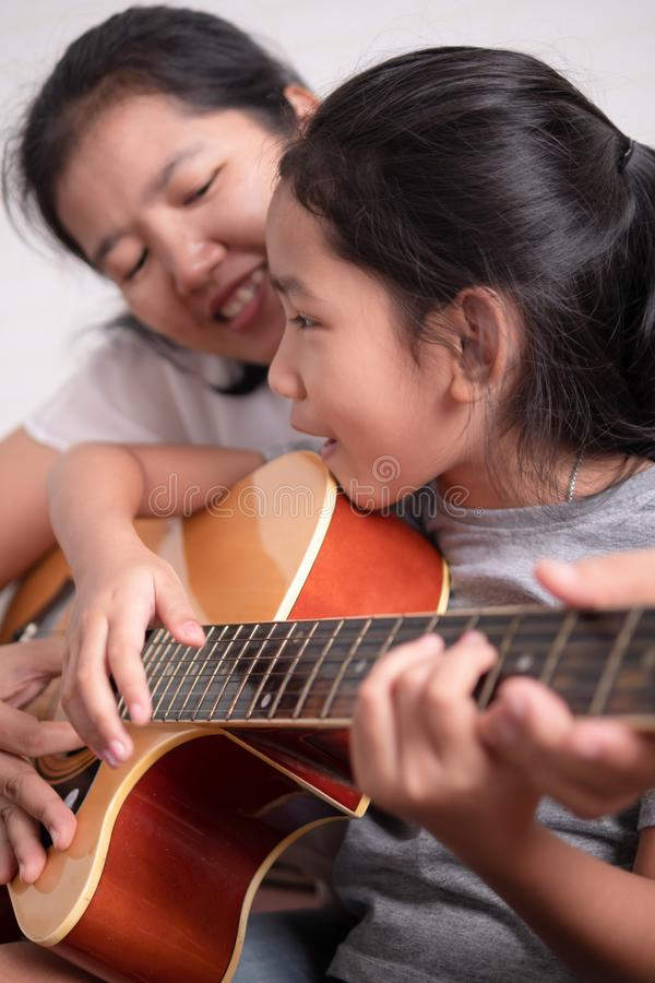 Children singing and smiling with mother. Mom and daughter playing a guitar with happiness on holiday. Asian little girl learning to play music. Children singing royalty free stock images