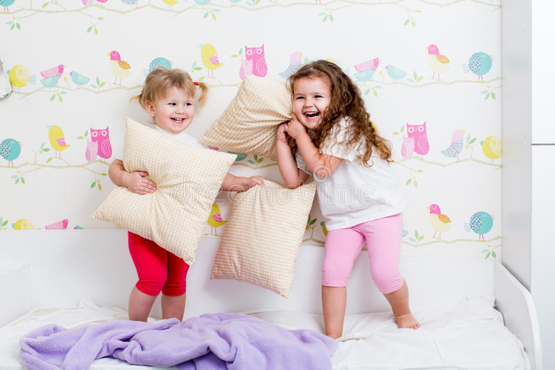 Download Children Sisters Play On The Bed Indoors Stock Photo   Image Of  Enjoying, Merry