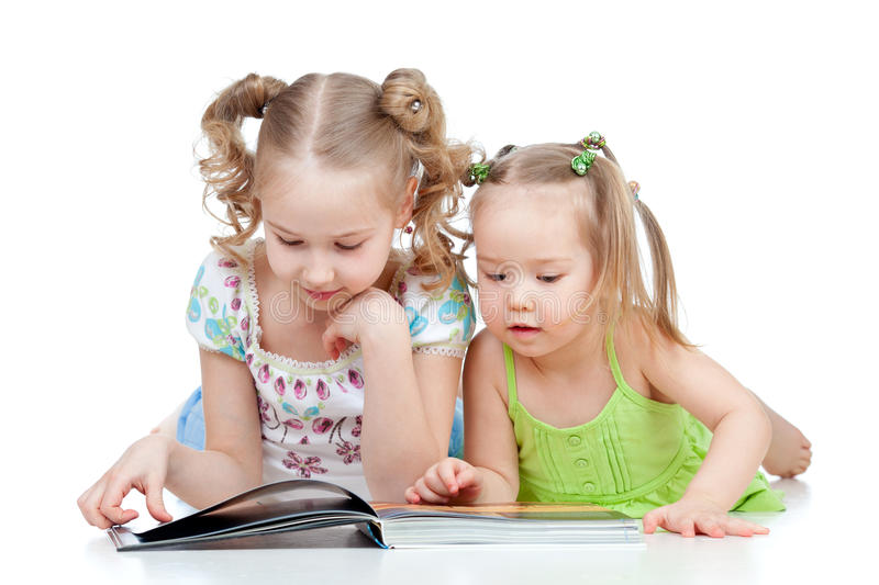 Children sisters reading a book together stock images