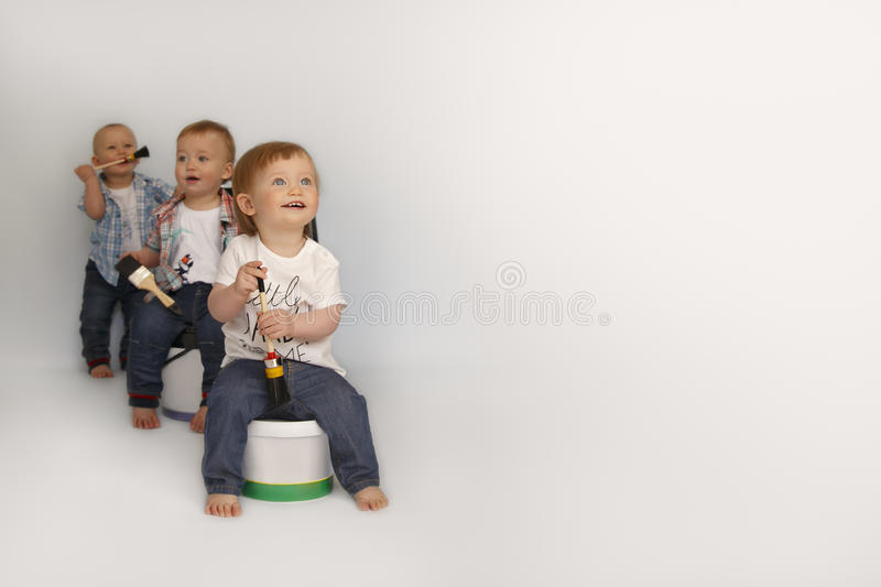 Children sit on large cans of paint royalty free stock photos
