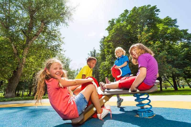 Children sit on playground carousel with springs stock images