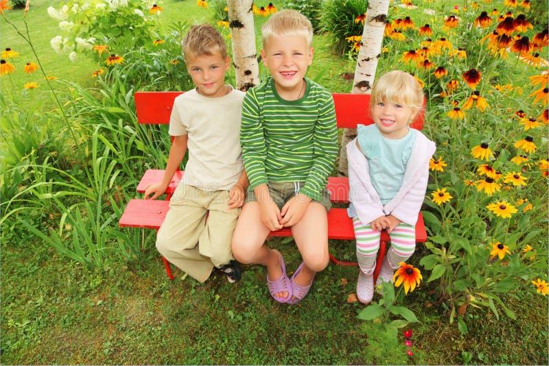 Children Sitting On Bench In Garden Stock Image