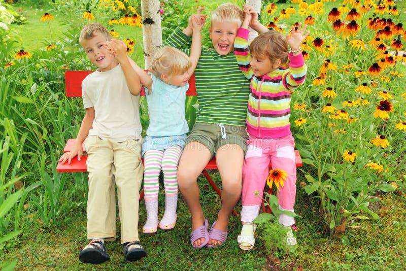 Download Children Sitting On Bench In Garden Stock Photo - Image: 12263446