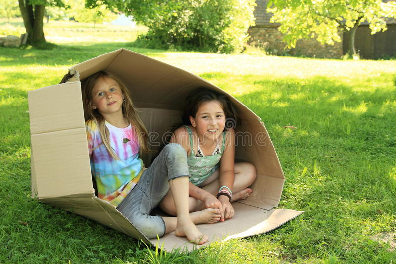 Children sitting in a box stock images