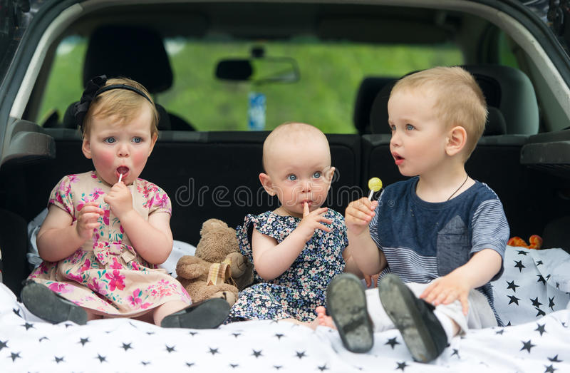 Children sitting in car trunk. Three kids eat candies. Cute children sitting in car trunk. Three kids eat candies royalty free stock photography