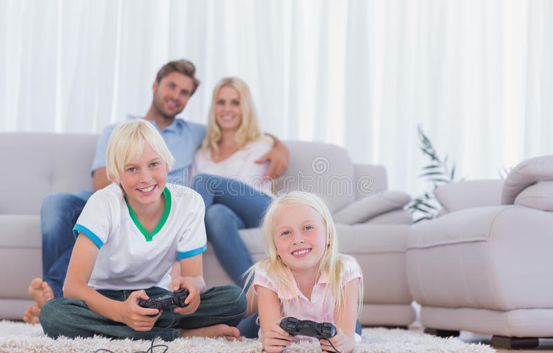 Download Children Sitting On The Carpet Playing Video Games Royalty Free Stock Photo - Image: 31802135