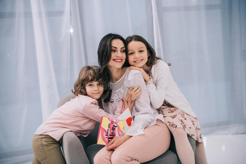 Children sitting on comfy armchair with mother. On mothers day stock photos