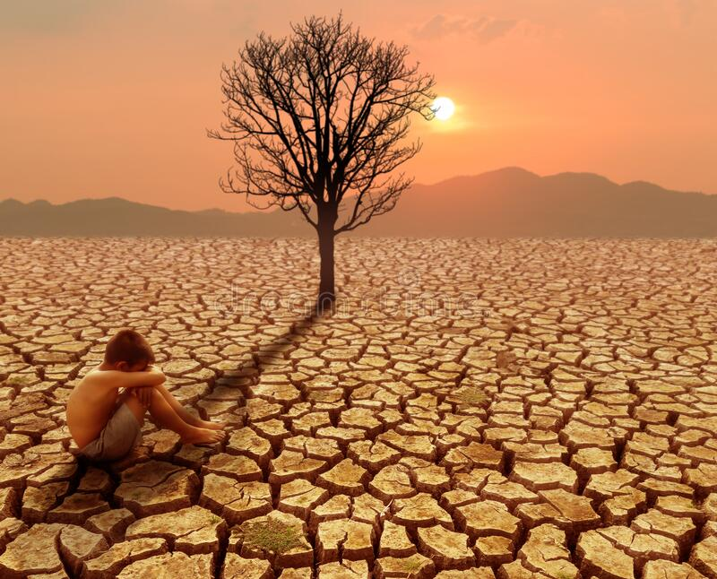 Children sitting on crack earth in arid area with dead tree and hot climate. Climate change and global warming concept stock images