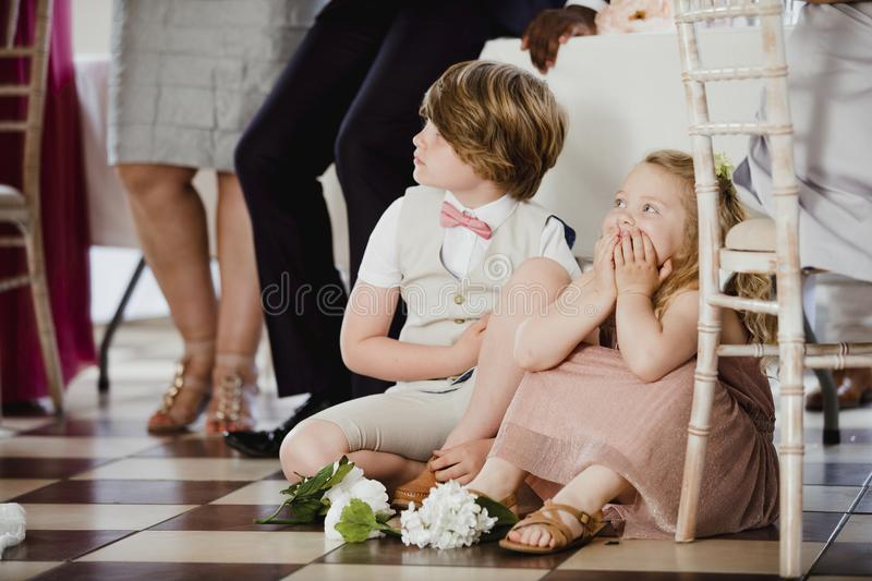 Children Watching at a Wedding. Children are sitting on the dancefloor by a table at a wedding. They are watching the bride and groom share their first dance stock photo