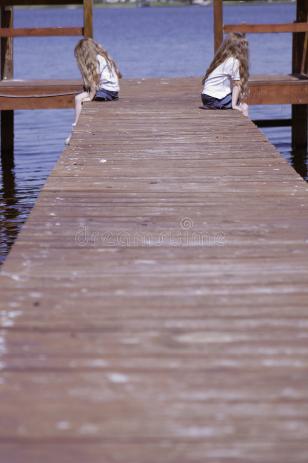 Children sitting on end of dock stock photo