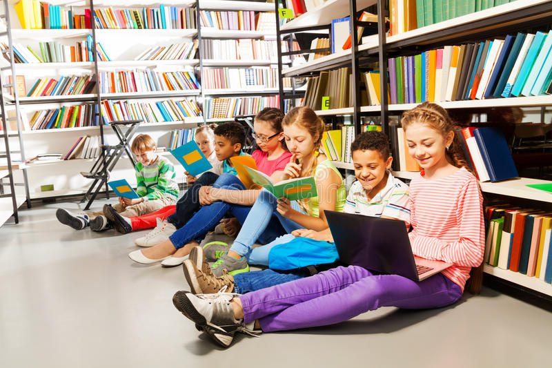 Children sitting on floor in library and studying stock photos